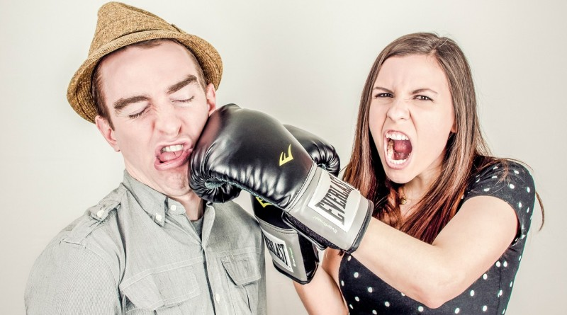 Woman punches man with boxing glove